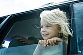 Child sticking head out of car window