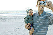 Man holding baby and using camera on beach