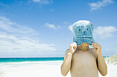 Child pulling hat over face at beach