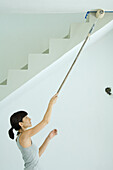 Woman painting ceiling with roller extension