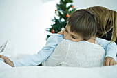 Mother sitting on sofa, holding boy in arms, Christmas tree in background, boy holding star