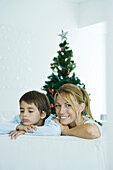 Boy and mother on sofa, Christmas tree in background, woman smiling at camera, boy frowning