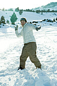 Young man throwing snowball, smiling at camera, full length