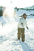 Young man throwing snowball, blurred motion, full length