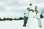 Three young friends leaning against snowman, smiling at camera, portrait