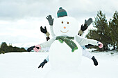 Young friends hiding behind snowman, arms out