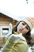 Teenage girl in winter clothes blowing kiss to camera