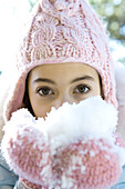 Preteen girl eating snow out of mittened hands, looking at camera