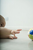 Baby lying on floor, reaching for ball, cropped view