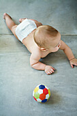 Baby lying on floor, ball nearby