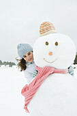 Female embracing snowman, smiling at camera, portrait