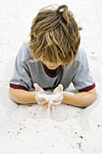 Boy lying on the ground, looking down at handful of sand