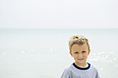 Young boy at the beach, smiling at camera, portrait