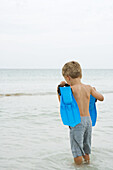 Young boy standing knee deep in water, carrying flippers, rear view