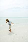Boy on beach throwing rock toward ocean, full length