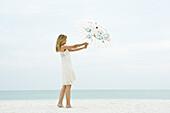 Woman holding parasol on beach, full length