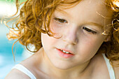 Little girl with red hair looking down, portrait