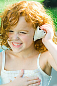 Little girl holding seashell up to ear, smiling, looking away