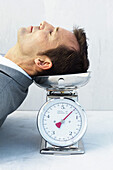 Man resting head on scale, eyes closed