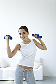Teen girl lifting dumbbells, smiling at camera