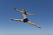 Young woman leaping, midair