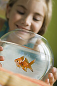 Girl watching goldfish swim in fishbowl