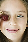 Girl covering eye with cherry, close-up