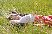 Young woman napping on blanket in tall grass