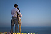 Couple standing on edge of infinity pool at dusk, looking at sea