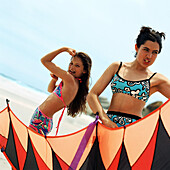Girl in bathing suit flexing arm muscles, teenager holding kite at the beach