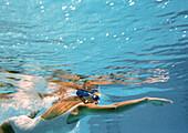Woman swimming underwater, underwater view.