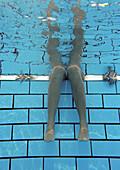 Woman, legs underwater, underwater view.