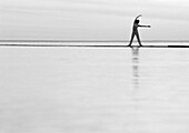 Woman exercising by the sea, b&w