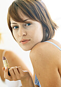 Woman holding lipstick, close-up, portrait