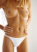 Partially nude woman standing with hands on hips, mid section, close-up.