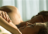 Couple lying together in bed, close-up