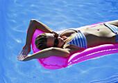Woman lying on air mattress in pool