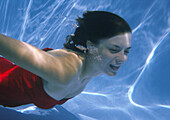Woman swimming underwater at bottom of pool