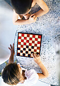 Two children playing checkers, view from directly above