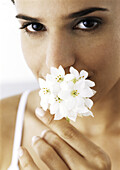 Woman holding white flowers to nose, looking at camera, close-up