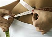 Woman measuring waist, close-up