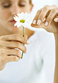 Woman plucking petals from flower with eyes closed