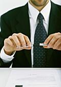 Businessman putting cap on pen, partial view