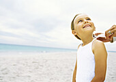 Girl standing on beach while mother ties shirt