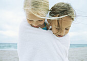 Two girls wrapped in same towel on beach