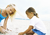 Two girls playing in sand