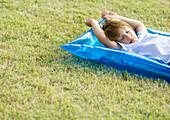 Little boy sleeping on inflatable raft, on grass
