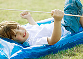 Little boy lying on inflatable raft, on grass