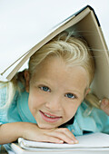 Girl holding book over head, smiling