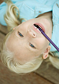 Little girl with head upside down and pencil in mouth
